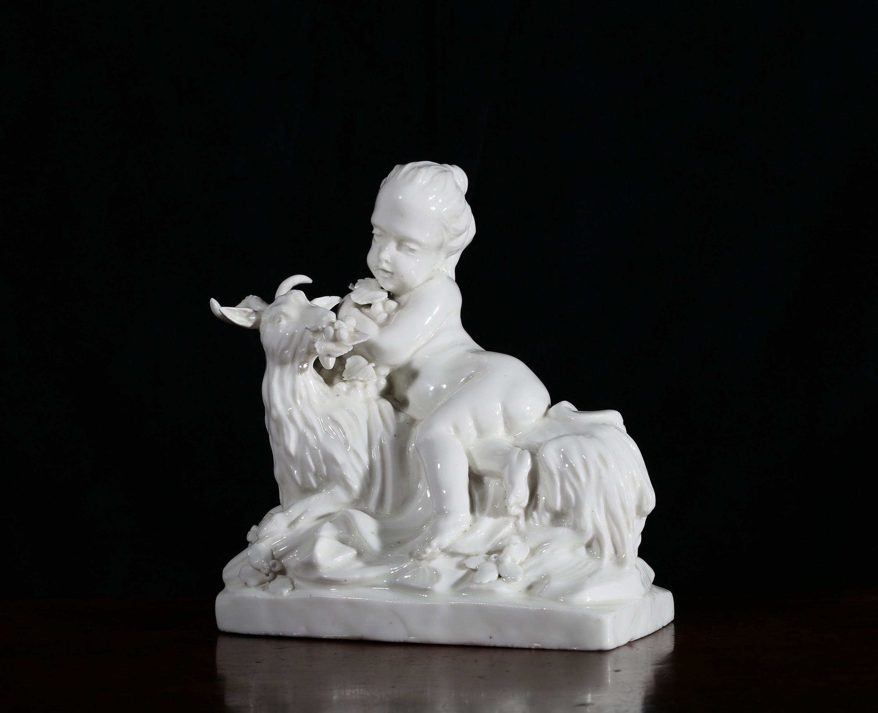 A white French figure of a child with a recumbent goat, probably Saint-Cloud