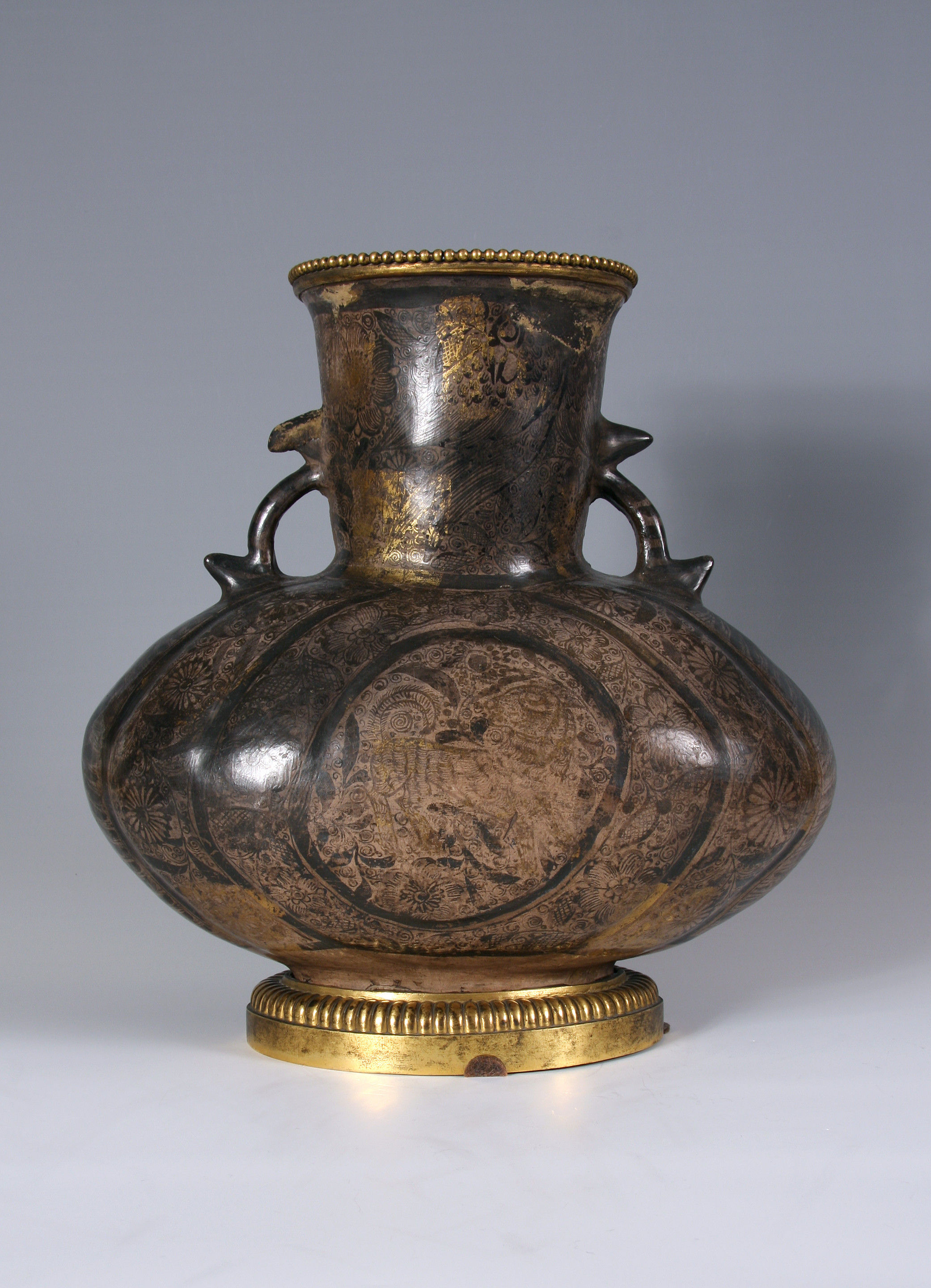 A Tonalá (Guadalajara) burnished earthenware two-handled vase, jarrón, densely painted in black with floral scrolls, birds and stylised lions with areas of applied gold leaf