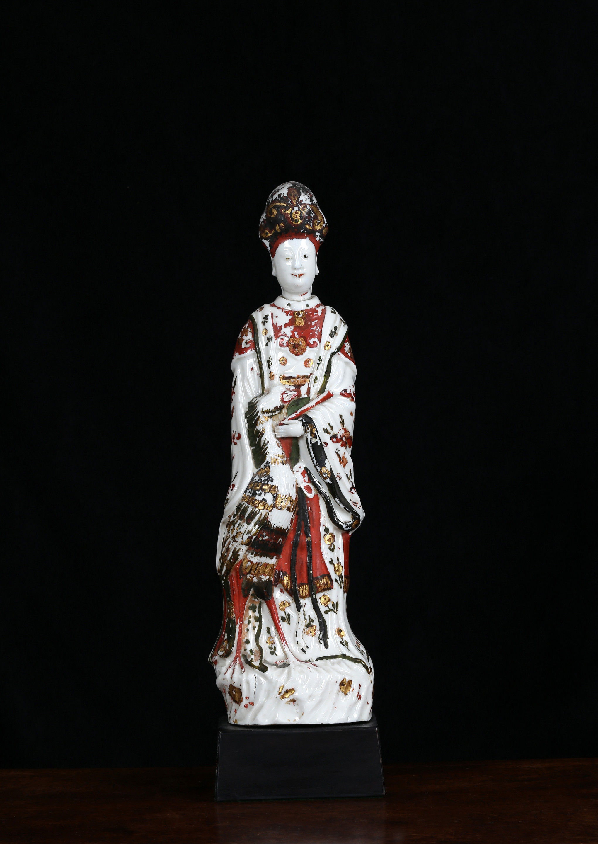 A cold-decorated Dehua figure of Guanyin standing beside a phoenix painted in black gold green and ochre